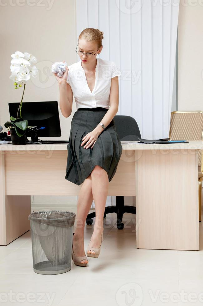 yong zakenvrouw gooien verfrommeld papier in een mand. foto
