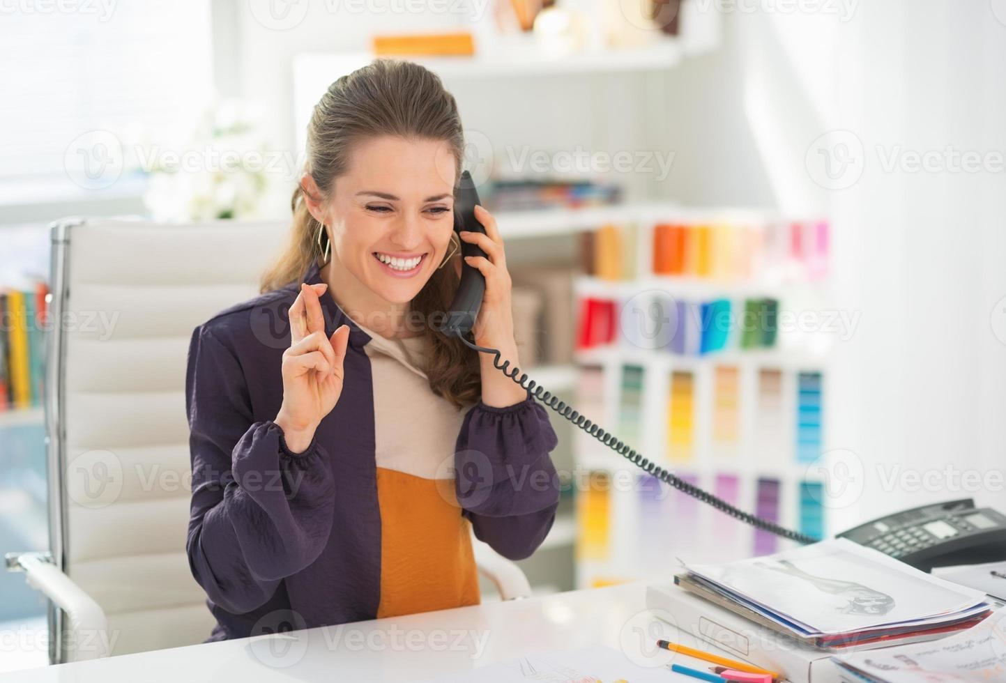 gelukkig modeontwerper praten telefoon met gekruiste vingers foto
