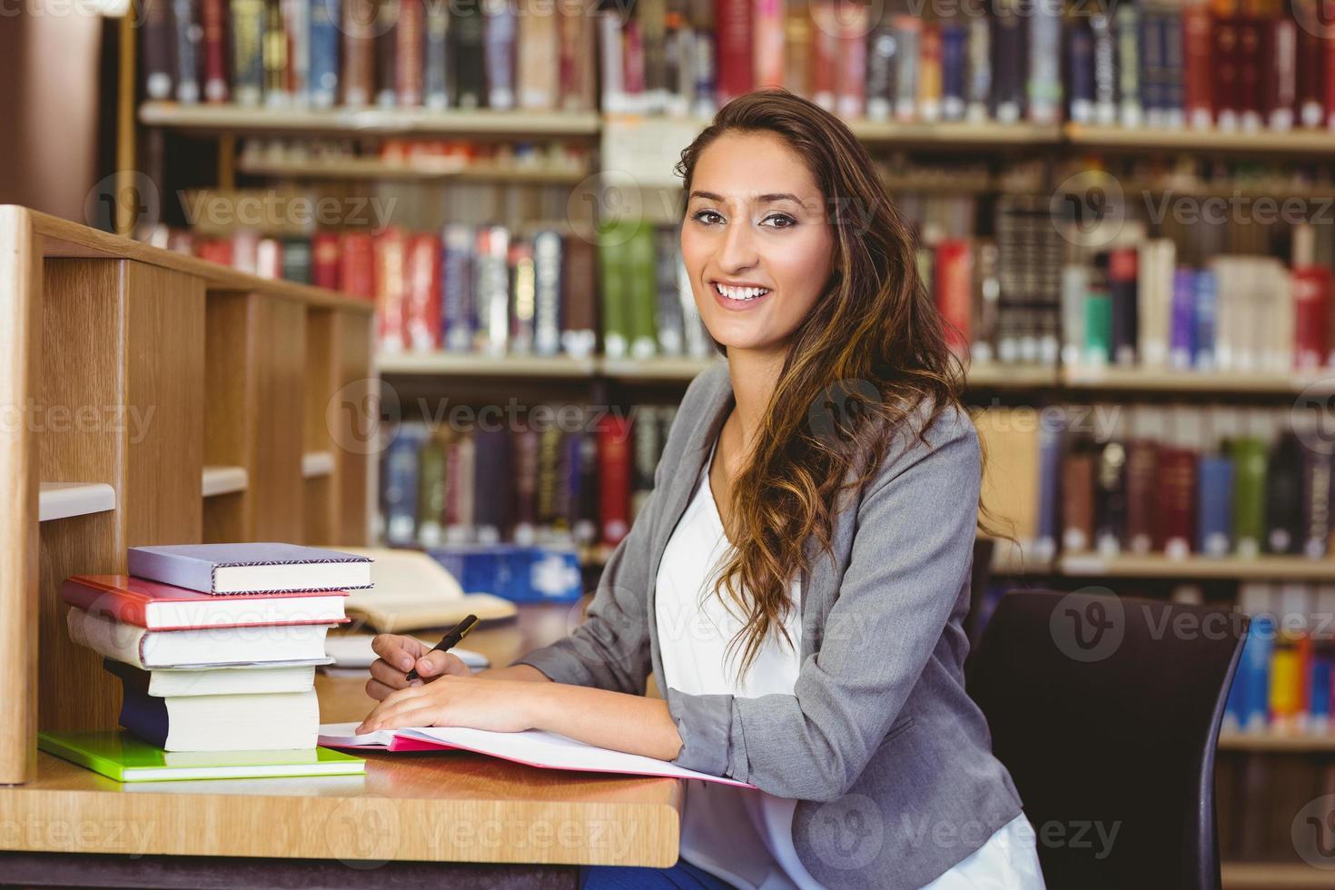 mooie student die in haar blocnote schrijft en bij camera glimlacht foto