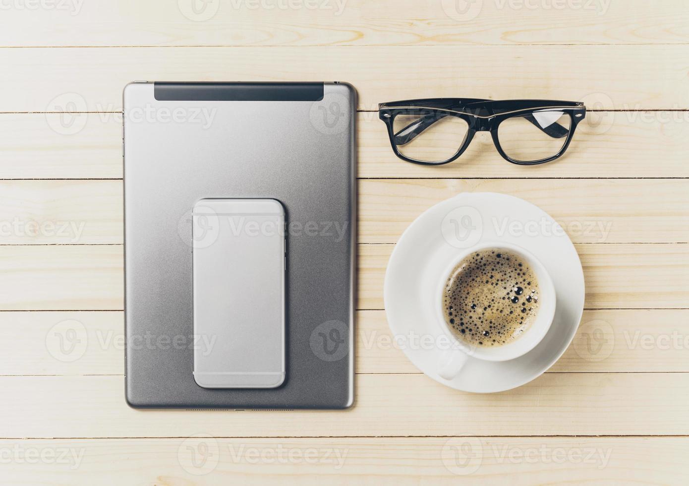 mobiele telefoon en tablet met notebook op het bureau foto