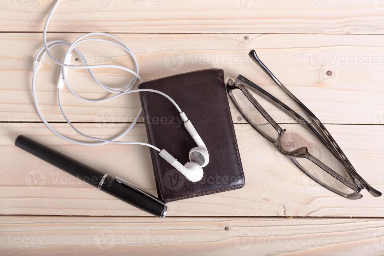 bruine portemonnee, bril, koptelefoon, pen foto