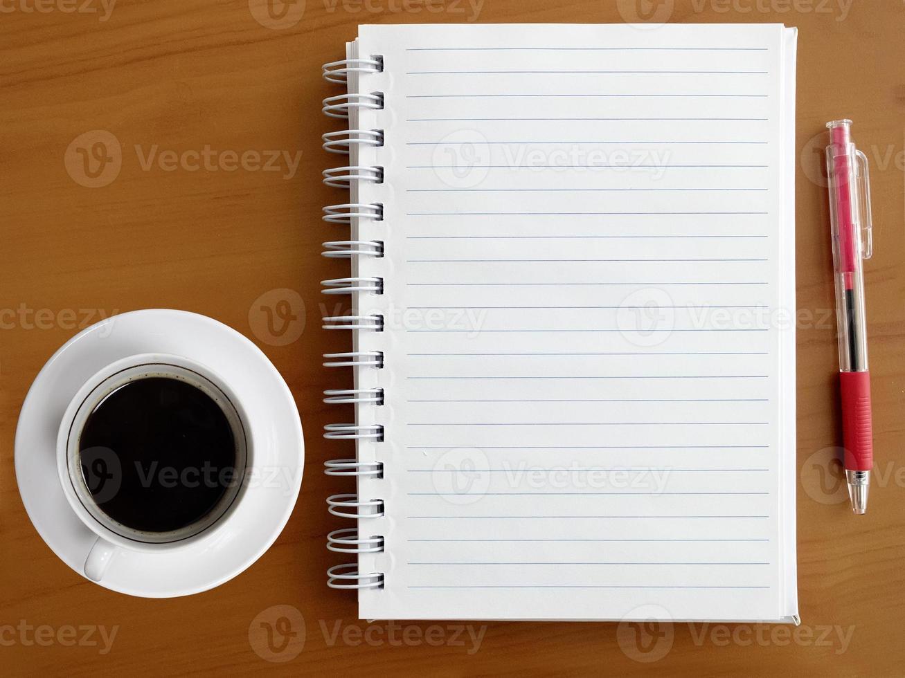 notebook, pen en kopje koffie op houten tafel foto