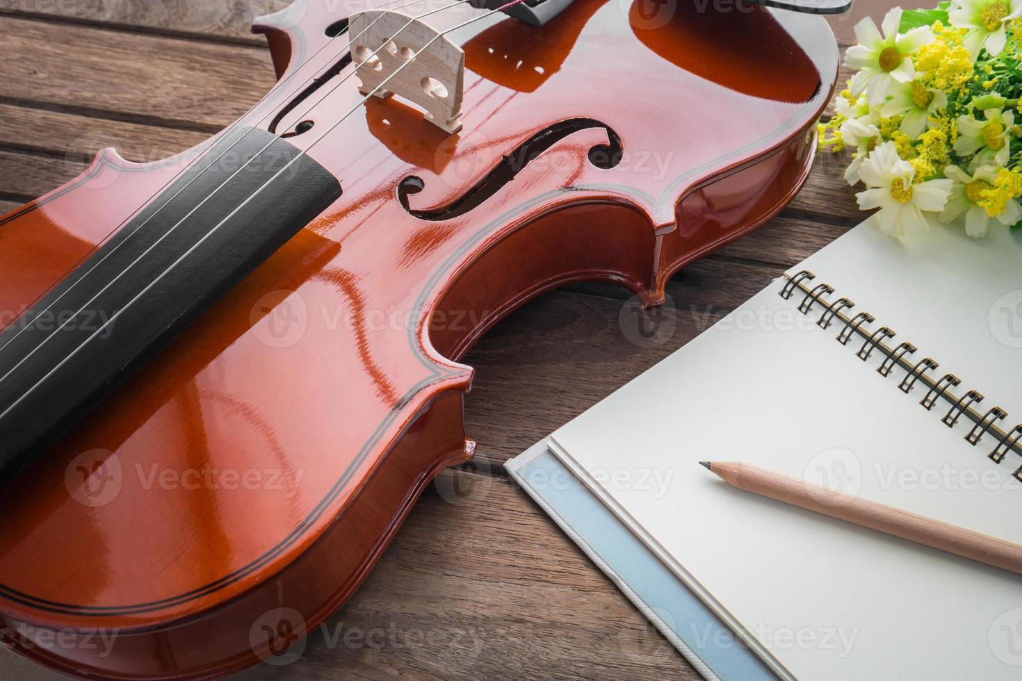 close up van viool en boek op houten tafel foto
