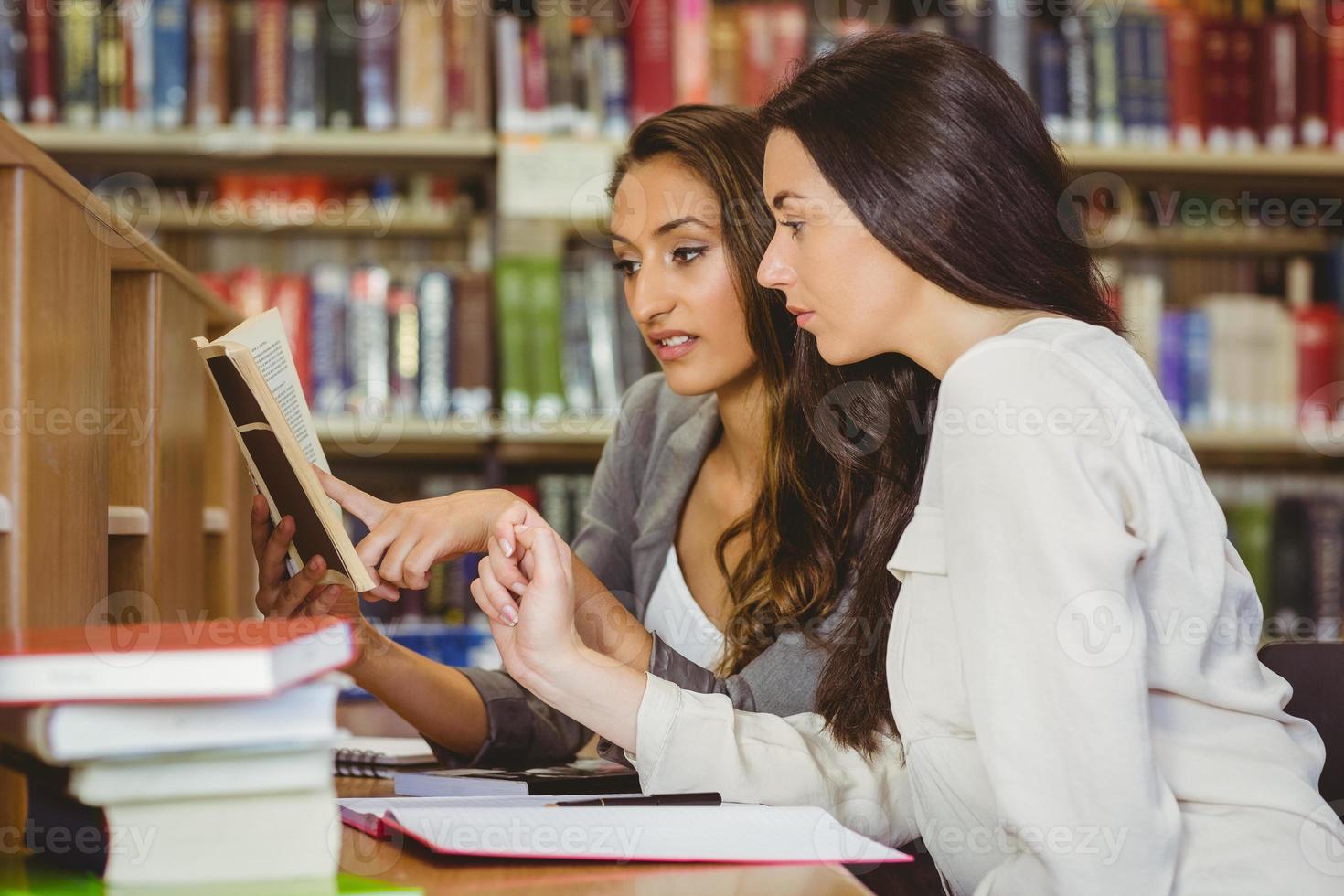 student toont iets aan haar klasgenoot in het boek foto