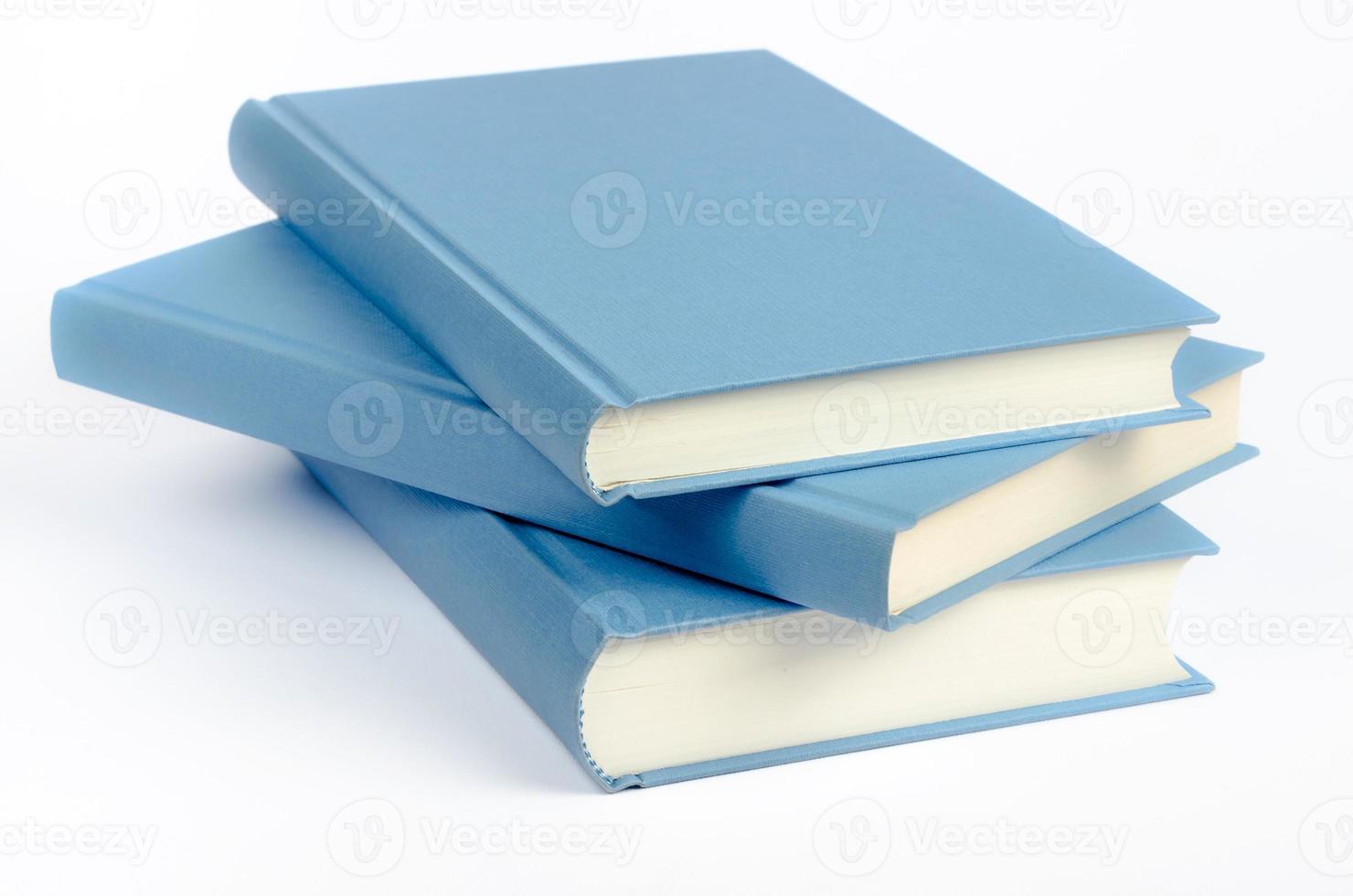 drie blauwe boeken op een witte achtergrond foto