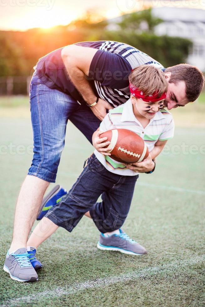 vader en zoon voetballen in het park foto