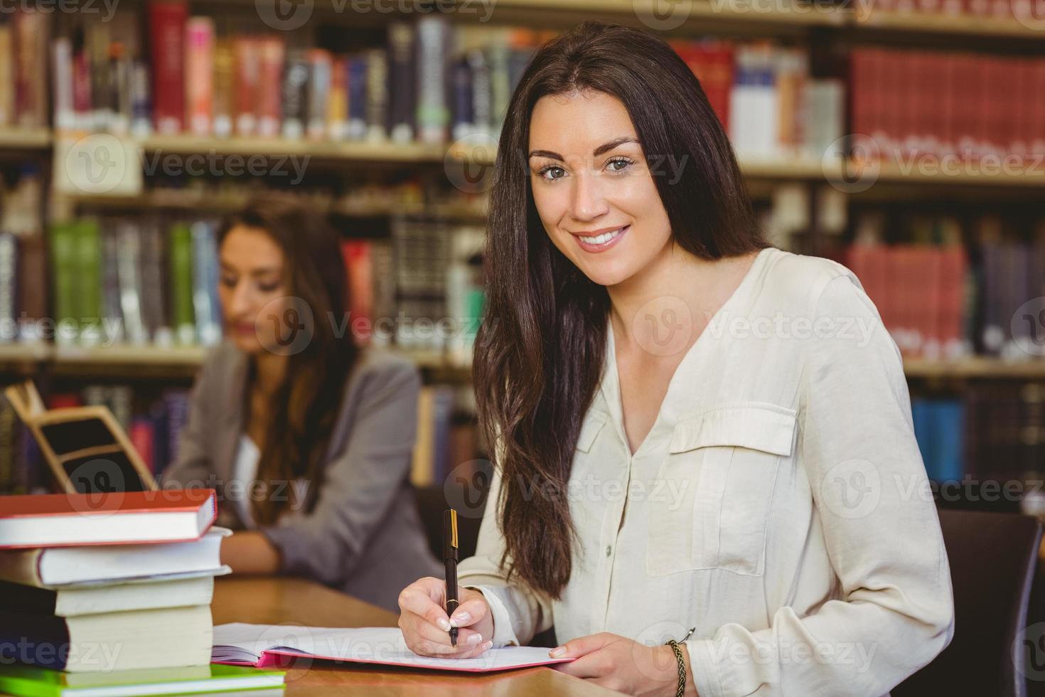 lachende mooie brunette student schrijven in Kladblok foto