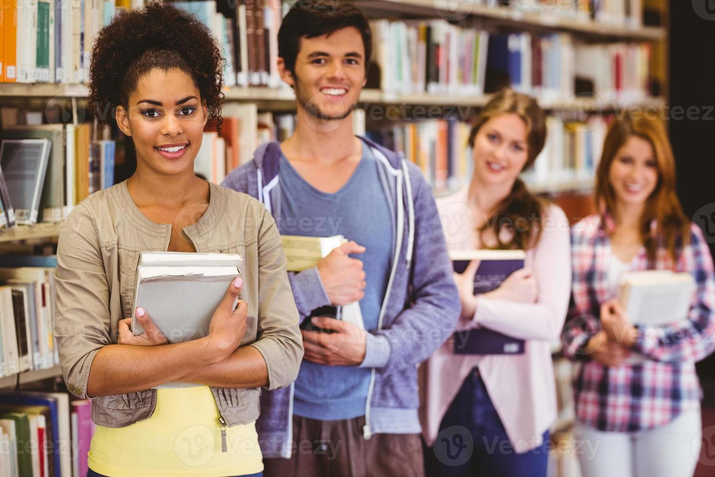 gelukkige studenten die boeken in rij houden foto
