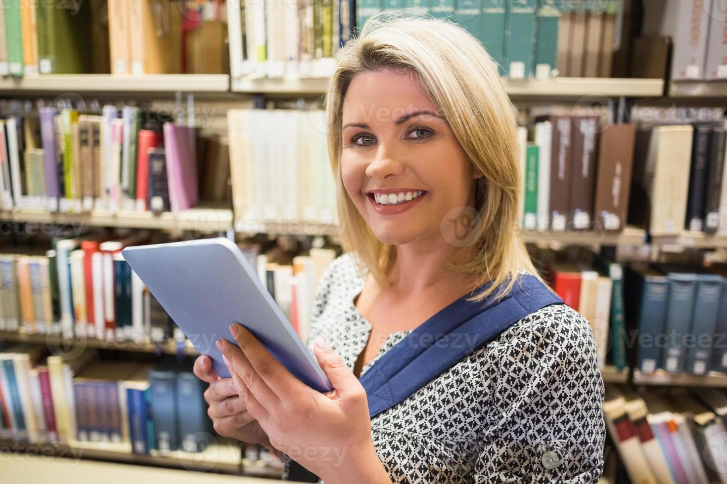volwassen student met behulp van tablet in bibliotheek foto
