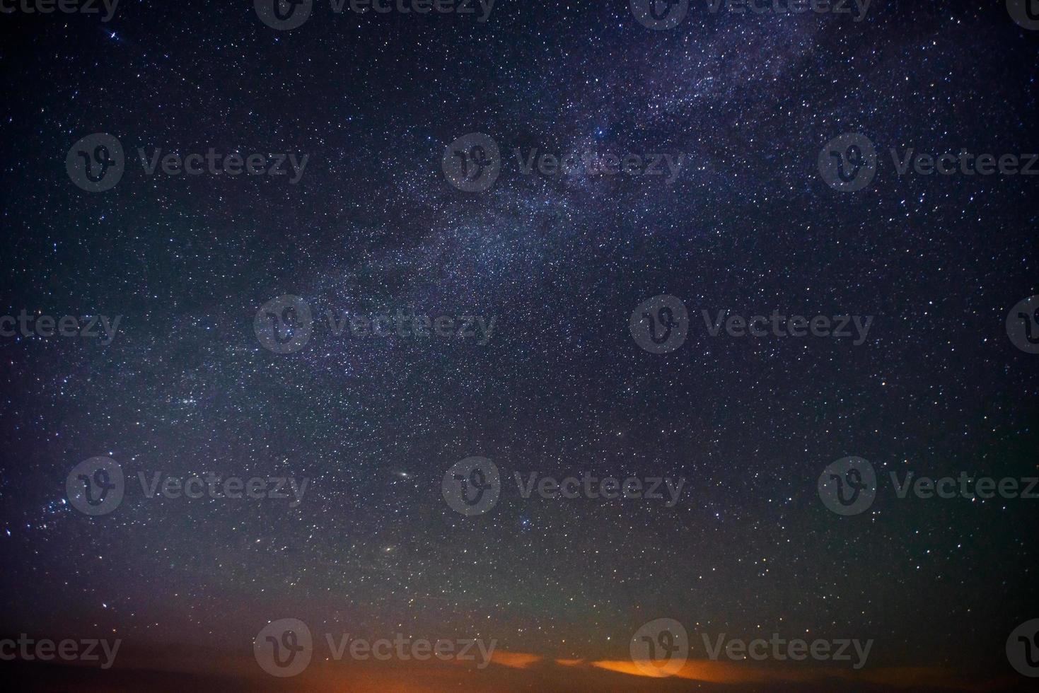sterren besprenkeld door donkerblauwe nachtelijke hemel foto