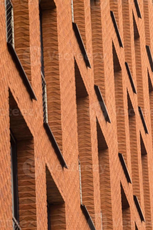 oranje bakstenen muur met ramen van modern gebouw foto