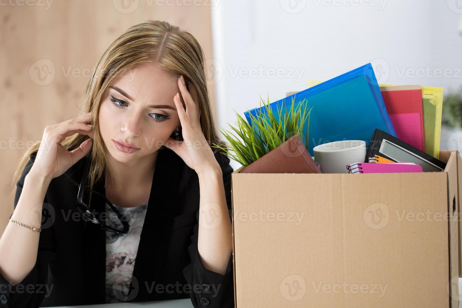 jonge ontslagen vrouwelijke werknemer zitten in de buurt van de kartonnen doos foto