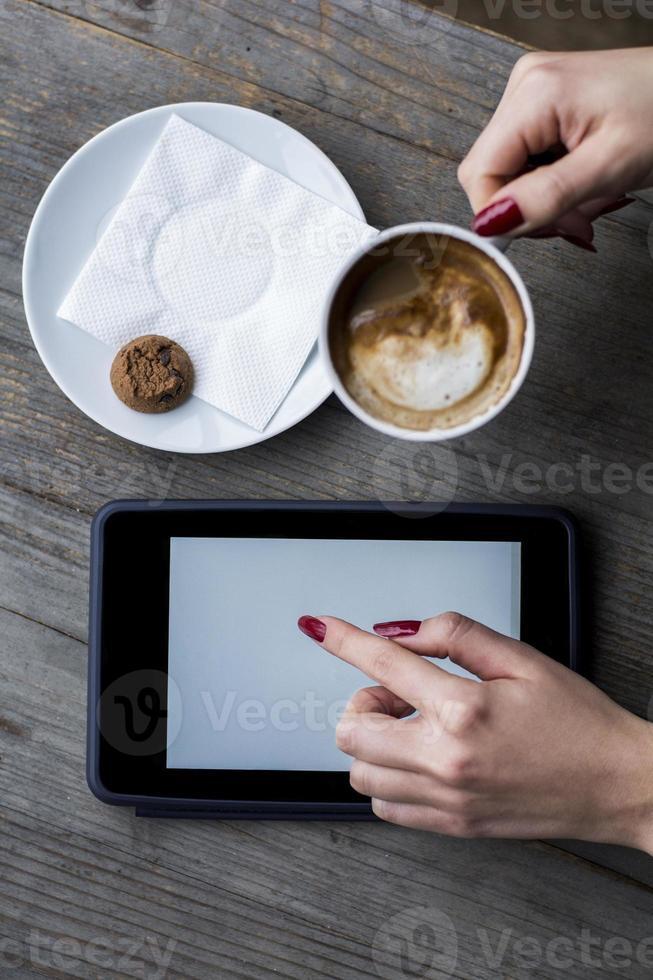 vrouw hand met koffie en zoeken op tablet foto