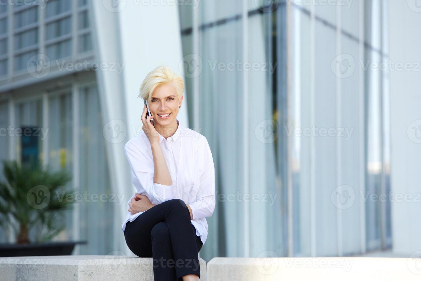 Glimlachende zakenvrouw buiten zitten met mobiele telefoon foto