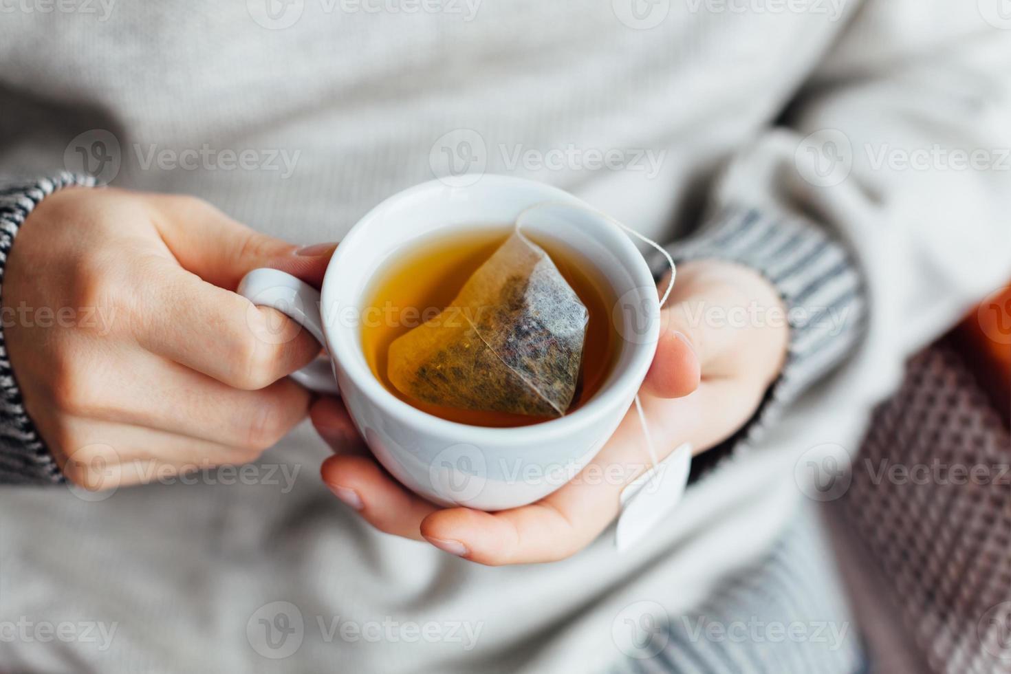 close-up van de mens die een kop hete thee houdt foto