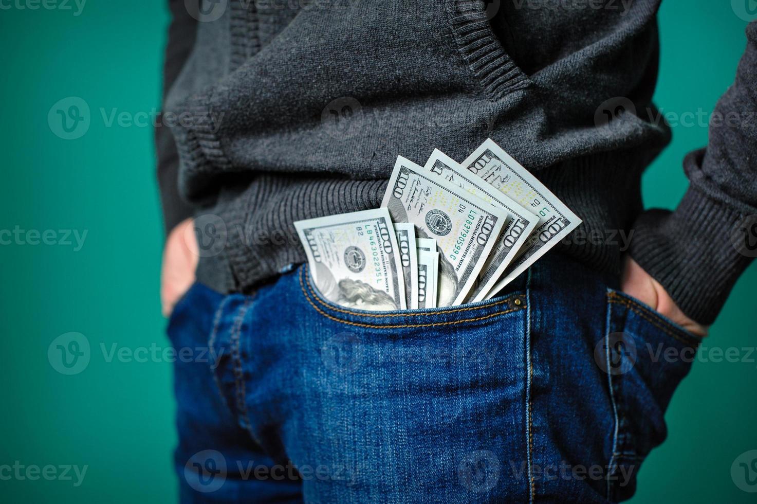 dollarbiljetten steken uit de zak van een man foto
