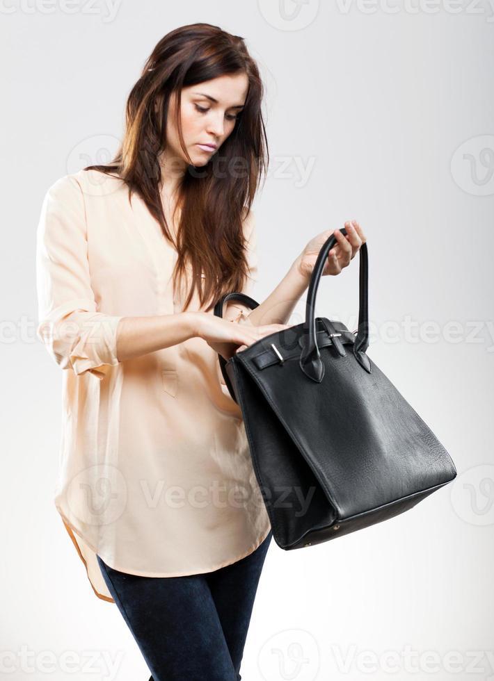 elegante jonge vrouw die in haar zak kijkt foto