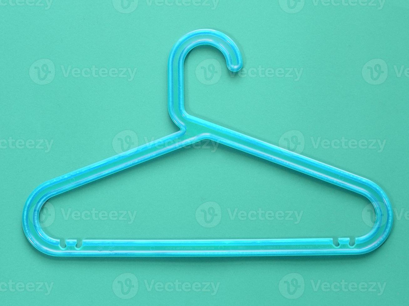 blauwe plastic kleerhanger op blauwe achtergrond foto