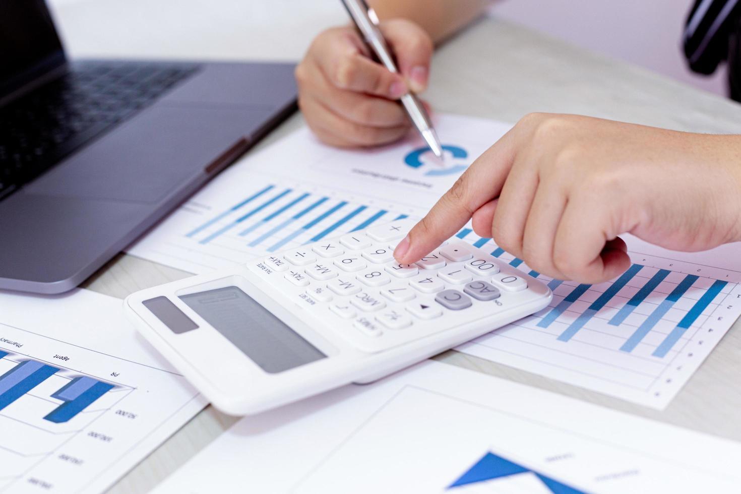 bedrijfspersoon gebruikt rekenmachine om financiële gegevens op het werk te analyseren foto