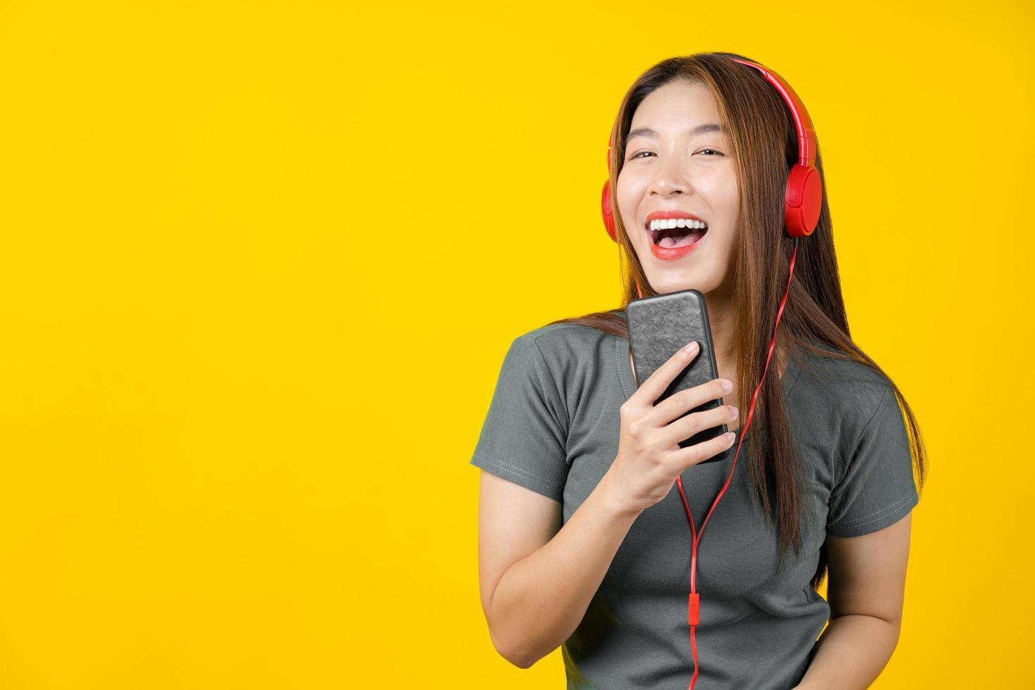 jonge Aziatische vrouw die aan muziek luistert foto