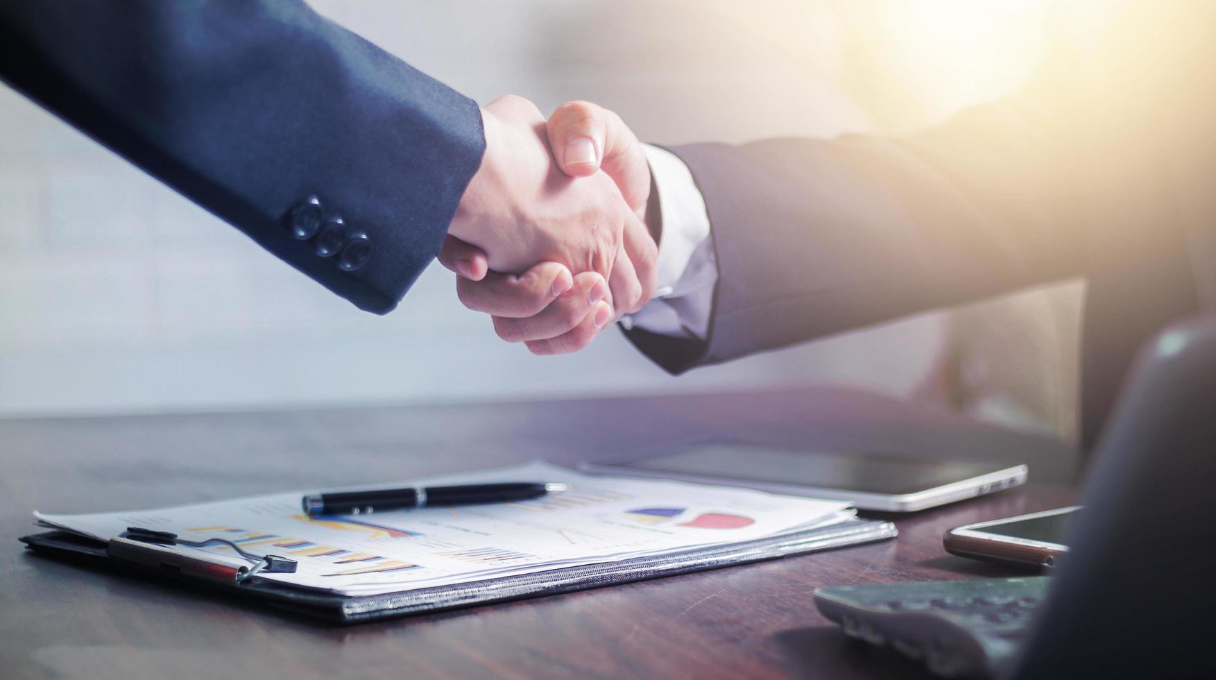 twee zakenlieden schudden elkaar de hand om een zakelijke deal te vieren foto