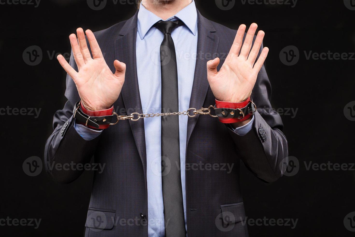 man in een pak met geketende handen. handboeien voor foto