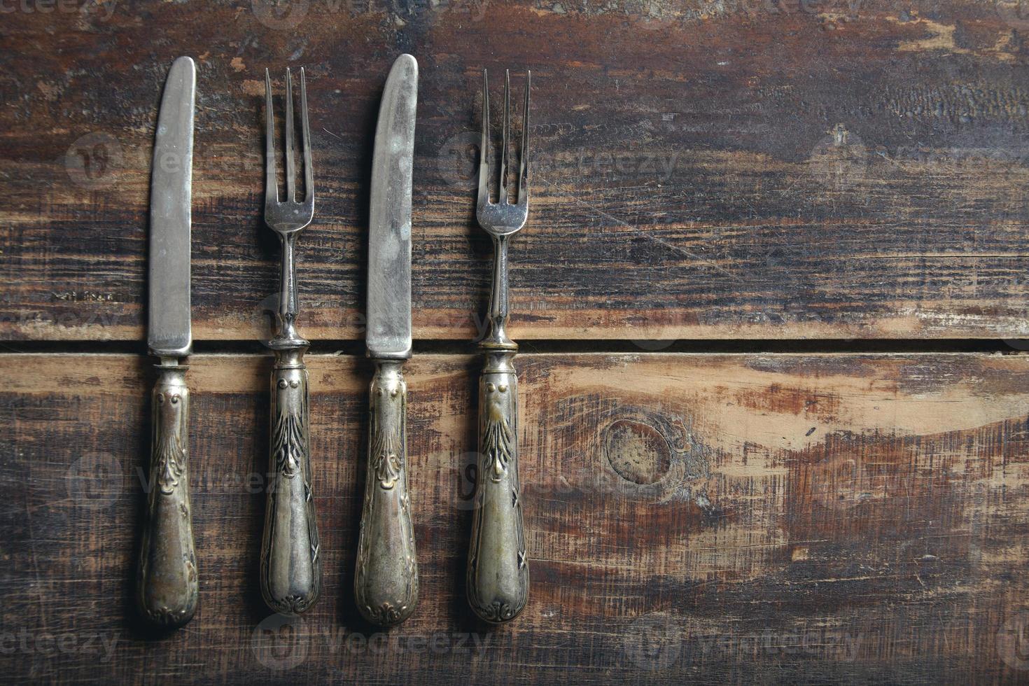 vorken en messen van bovenaf op een houten tafel foto