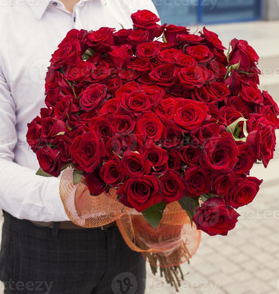 man in wit overhemd met boeket van rode rozen foto