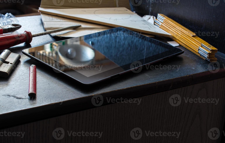 tablet op een donkere kast, omringd door gereedschap foto