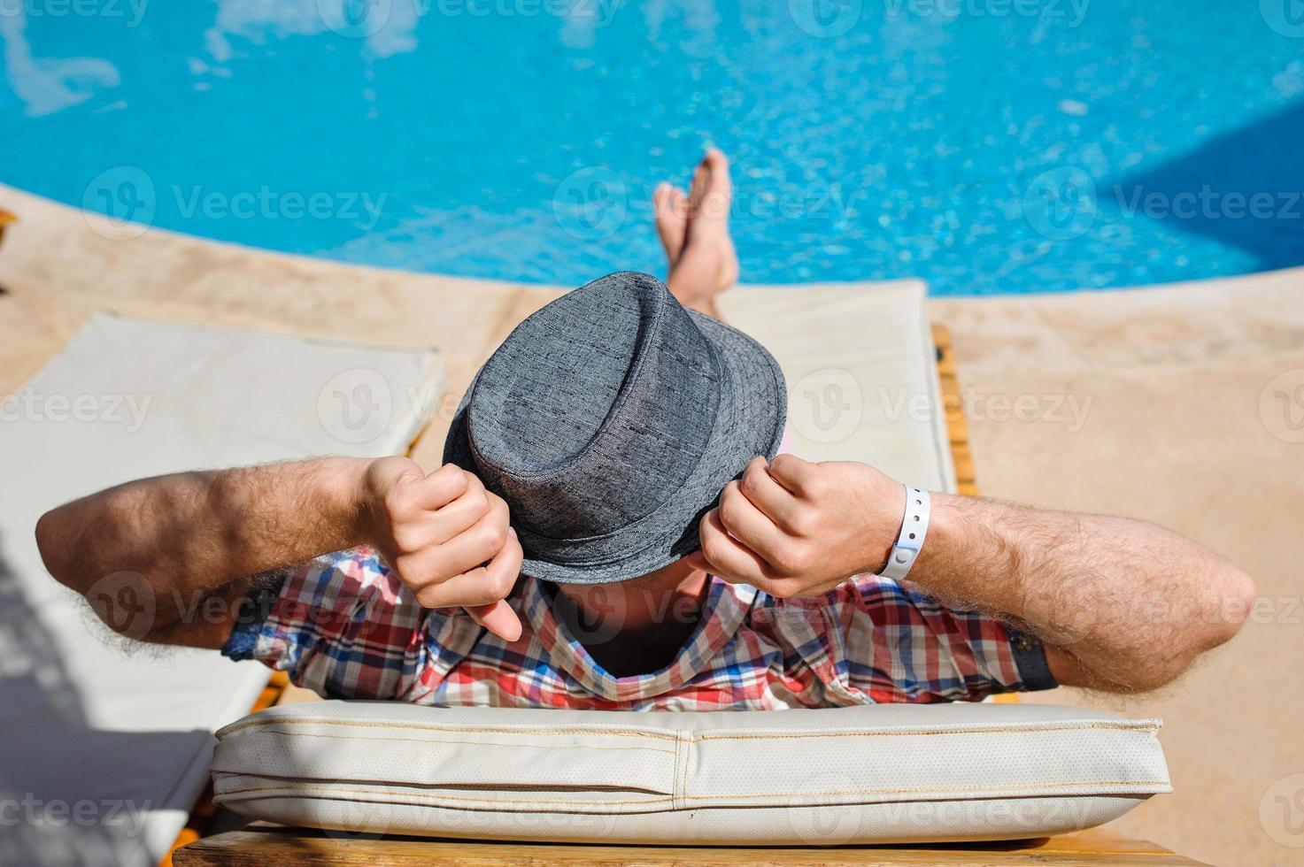 man in een hoed liggend op een ligstoel foto