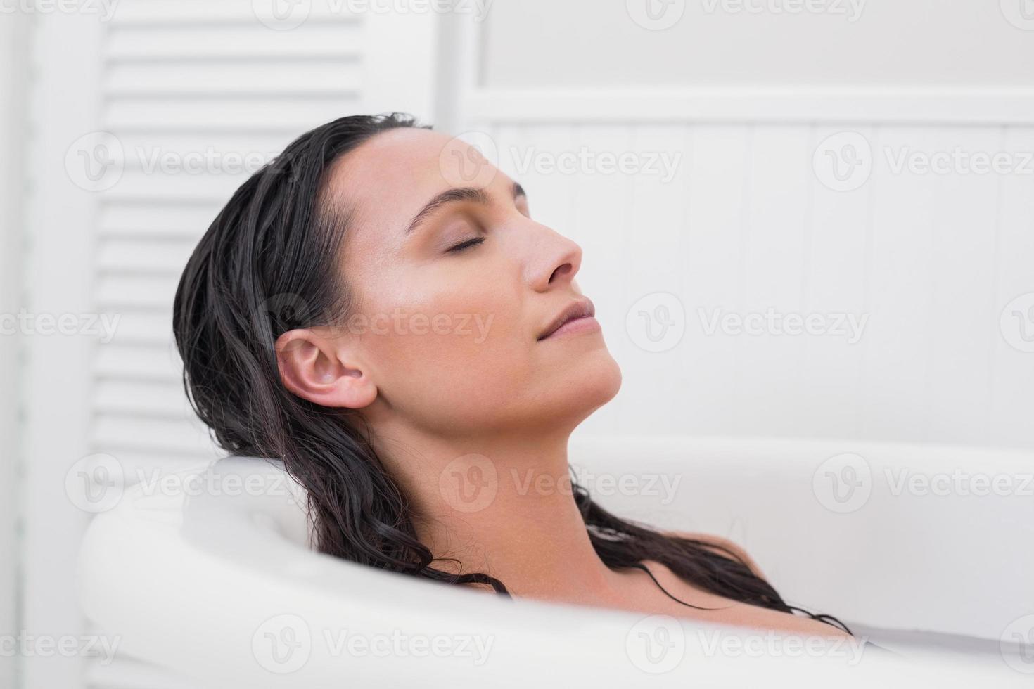 mooie brunette die een bad neemt foto