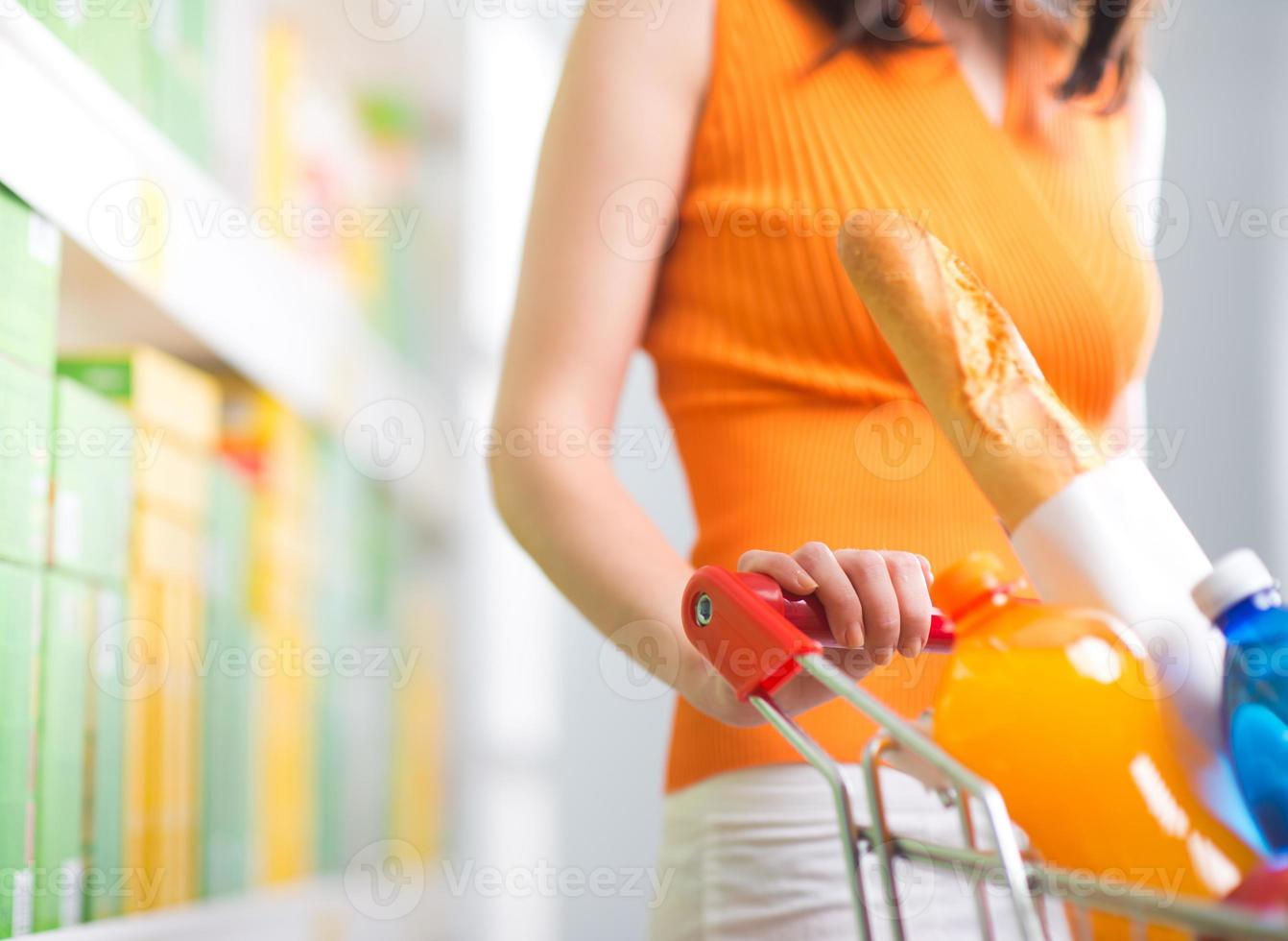vrouw bij supermarkt met trolley foto