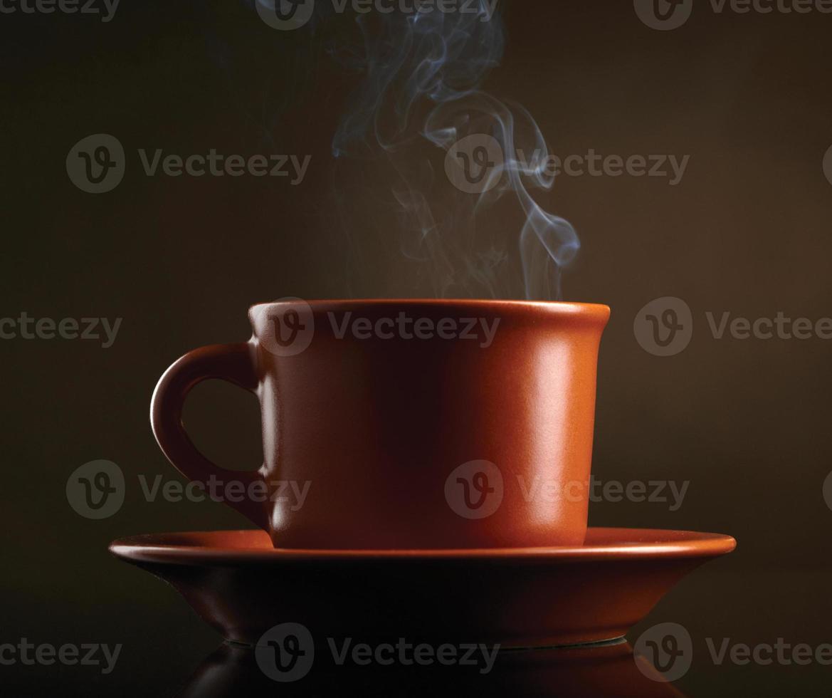 kopje koffie met rook op donkere achtergrond foto