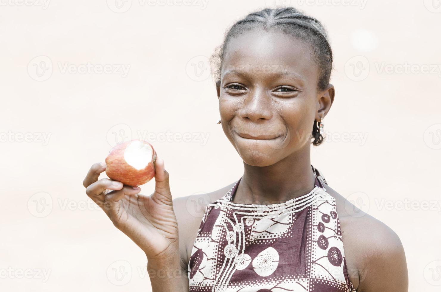 prachtig Afrikaans zwart schoolmeisje dat een appel bijt - gezondheidsachtergrond foto