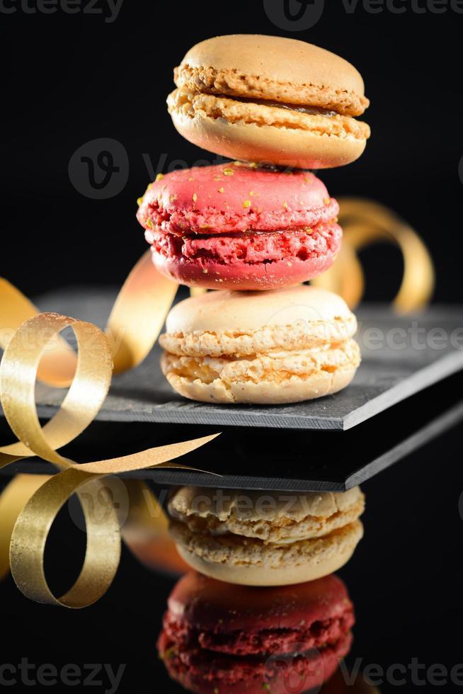 stapel kleurrijke Franse bitterkoekjes op leisteen met zwarte achtergrond foto