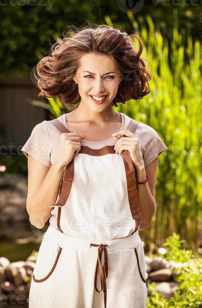 buitenshuis portret van mooie en positieve jonge vrouw in overall. foto