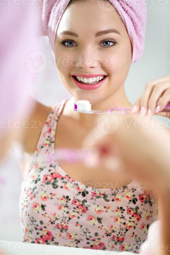 mooie jonge vrouw haar tanden poetsen foto