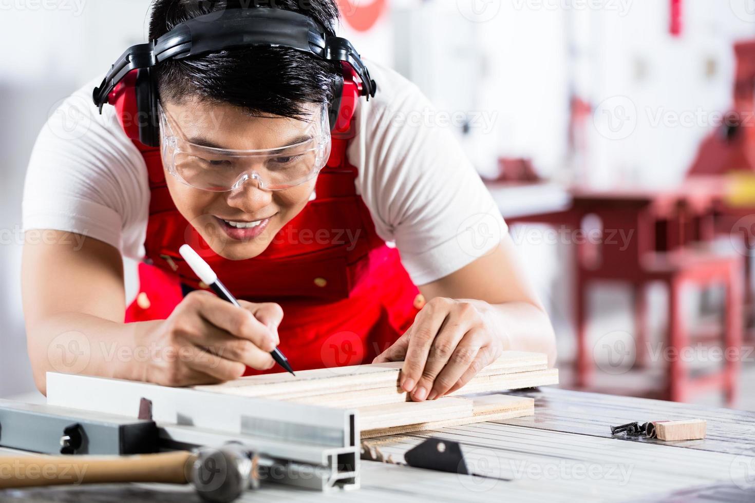 Aziatische Chinese timmerman snijden hout met zaag foto