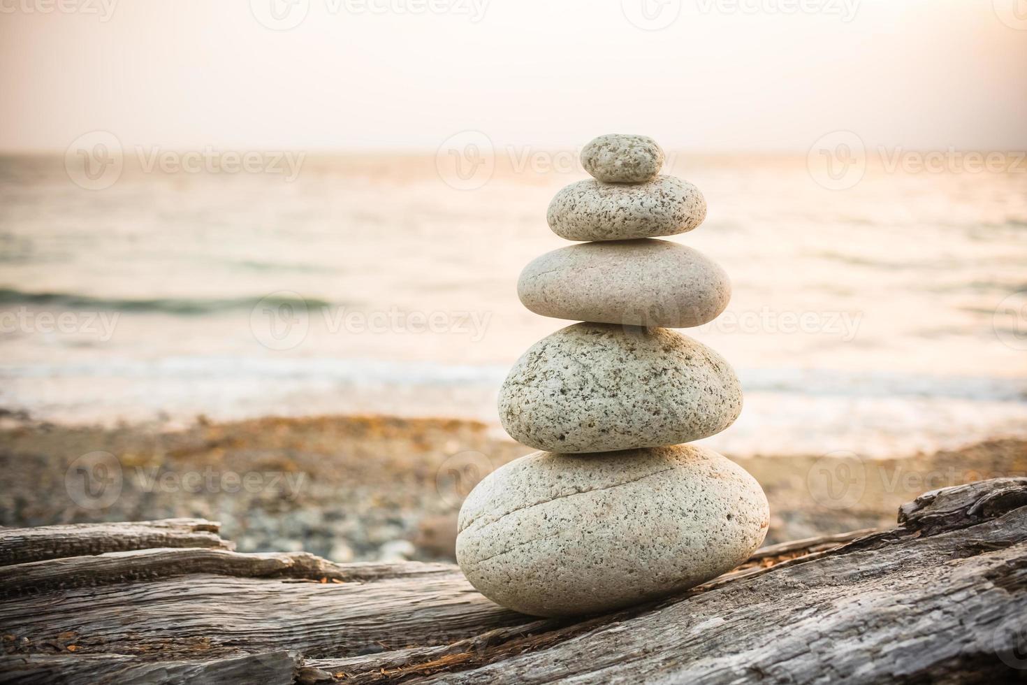 inukshuk steenhoop op drijfhout op strand foto