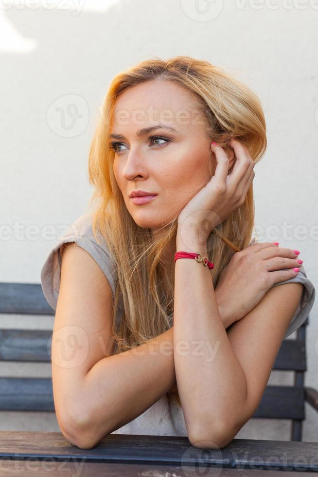 verdrietig meisje zit achter de tafel en ondersteunende hoofd-hand. foto