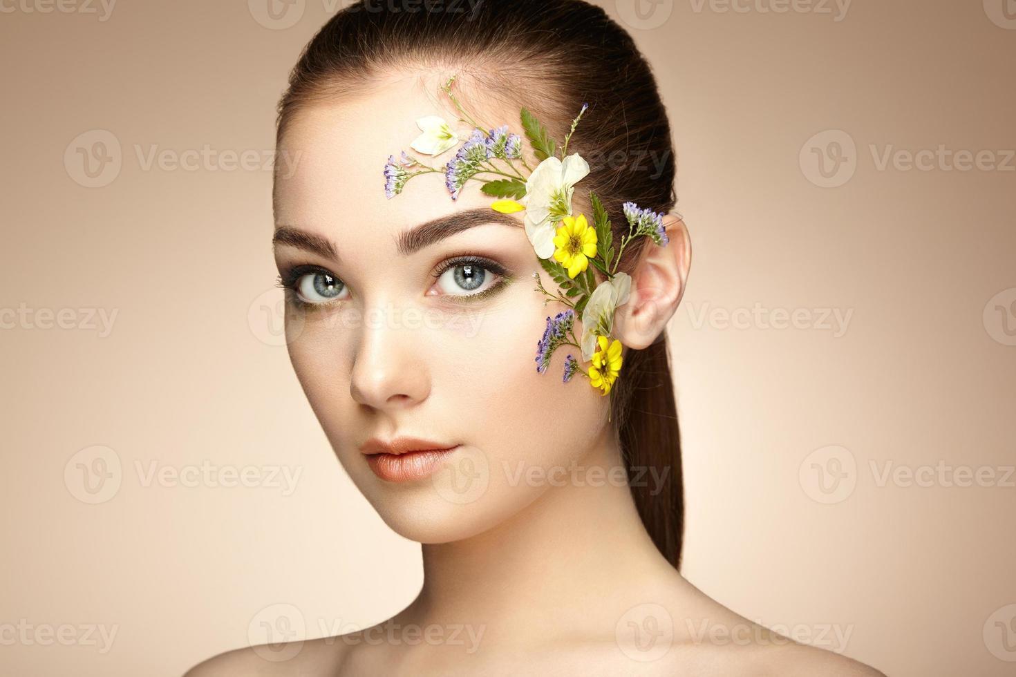 gezicht van mooie vrouw versierd met bloemen foto
