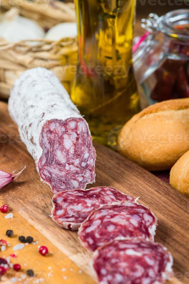 hele en gesneden salami met knoflook en olie met kruiden foto