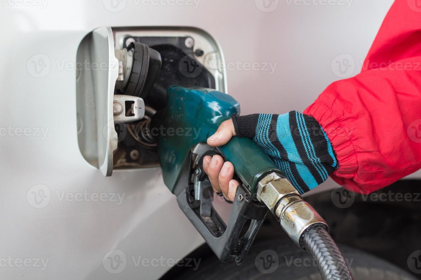 hand het bijvullen van de auto met brandstof op een tankstation foto