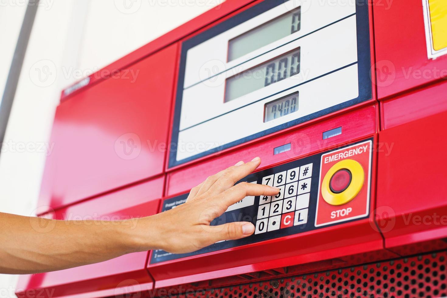 hand indrukken van knoppen op een brandstof bijvullen machine foto