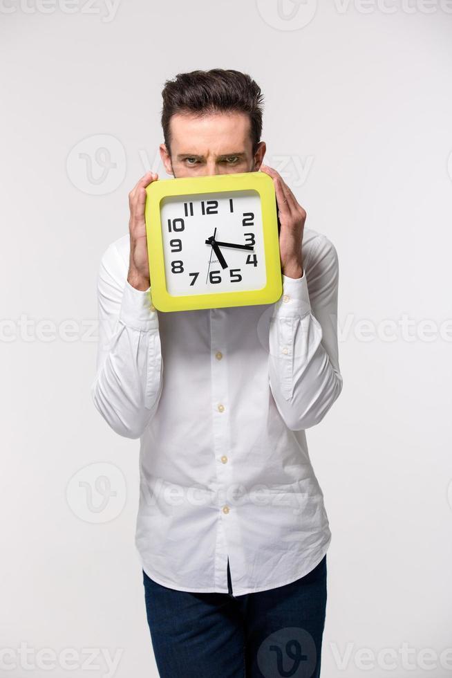 zakenman die zijn gezicht behandelt met muurklok foto