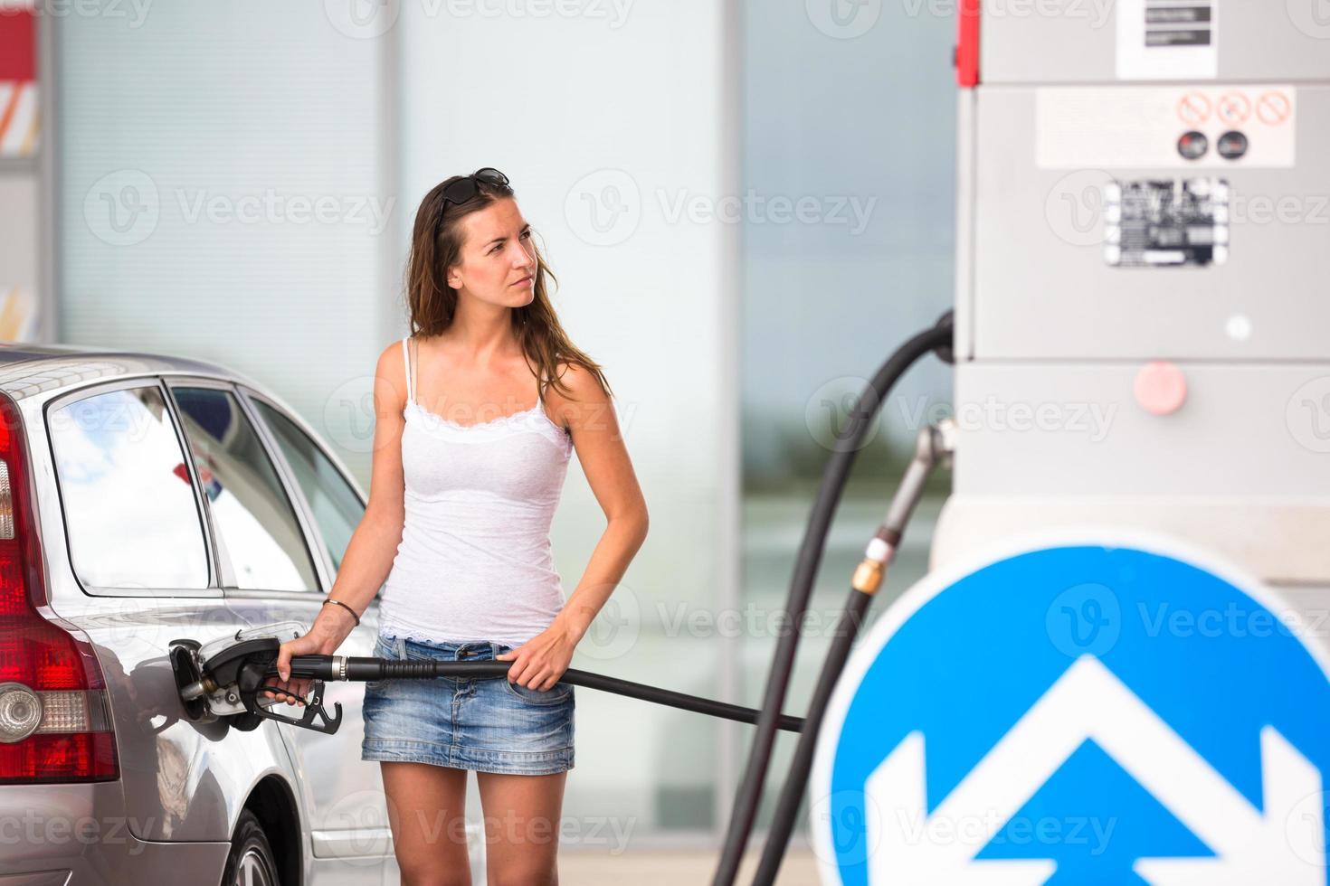 vrouw haar auto bijtanken in een tankstation foto