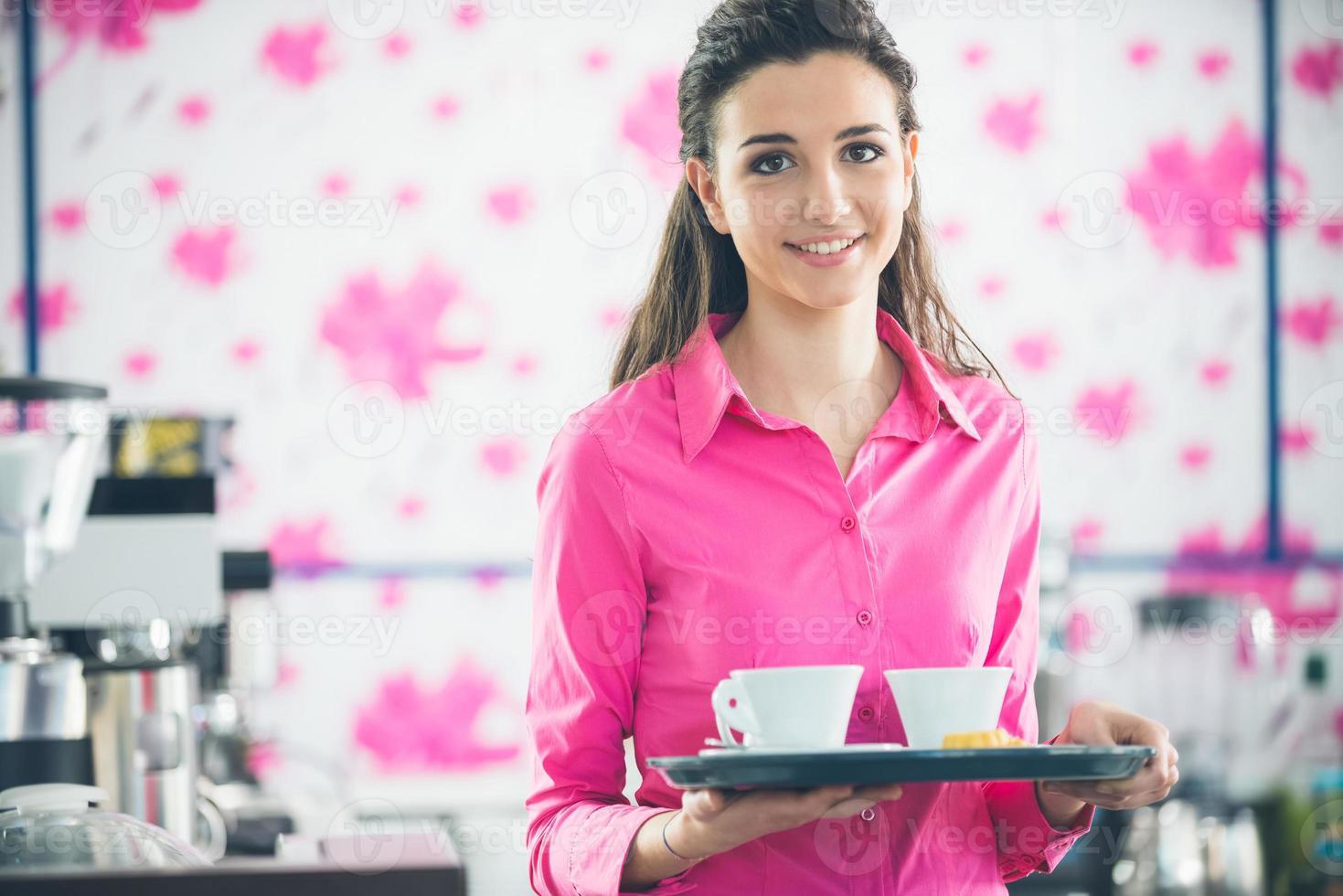 jonge glimlachende serveerster serveert koffie aan de bar foto