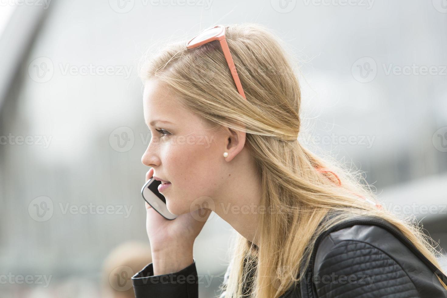 portret van jonge vrouw die op mobiele telefoon spreekt foto