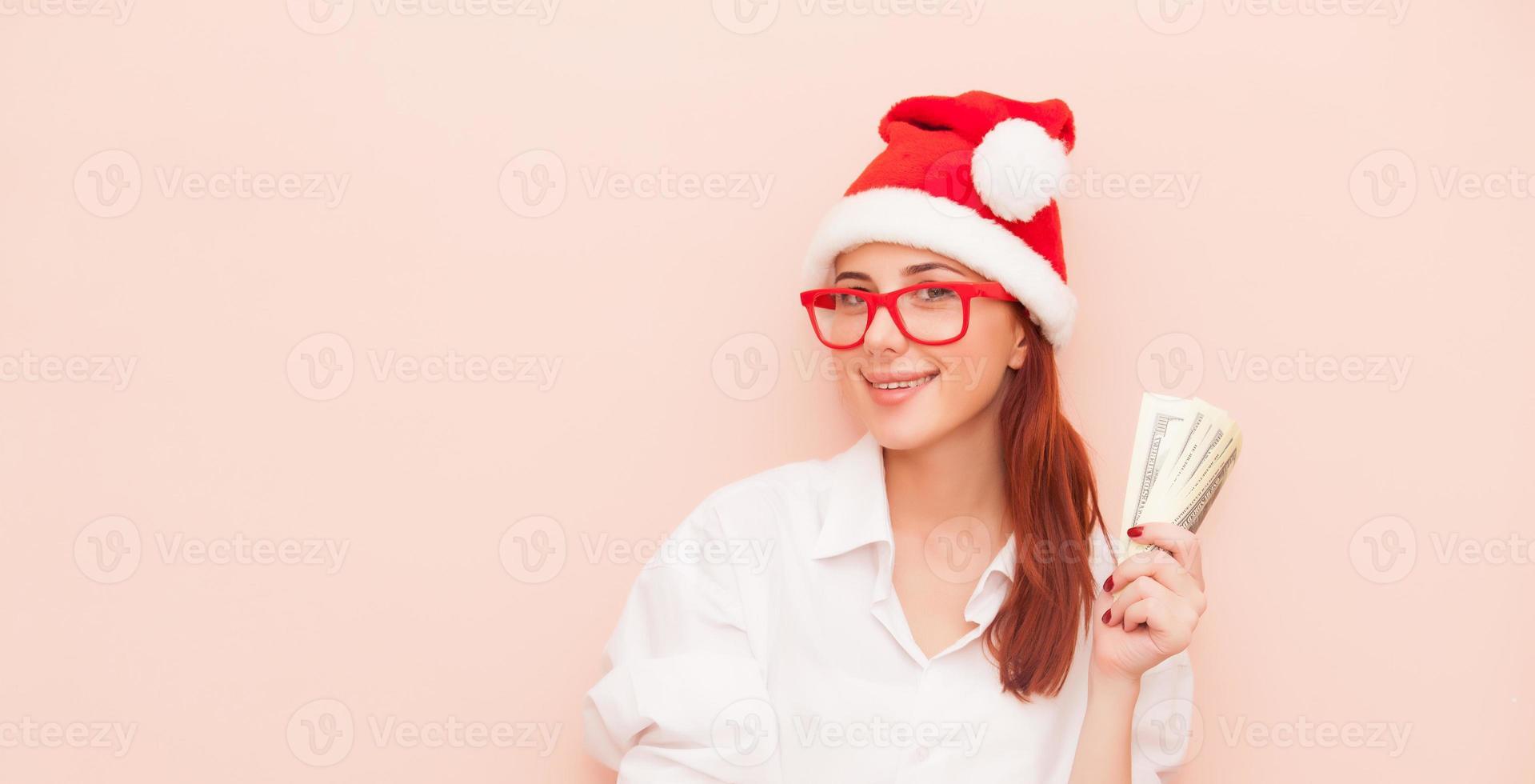 vrouw in Kerstman hoed met geld foto