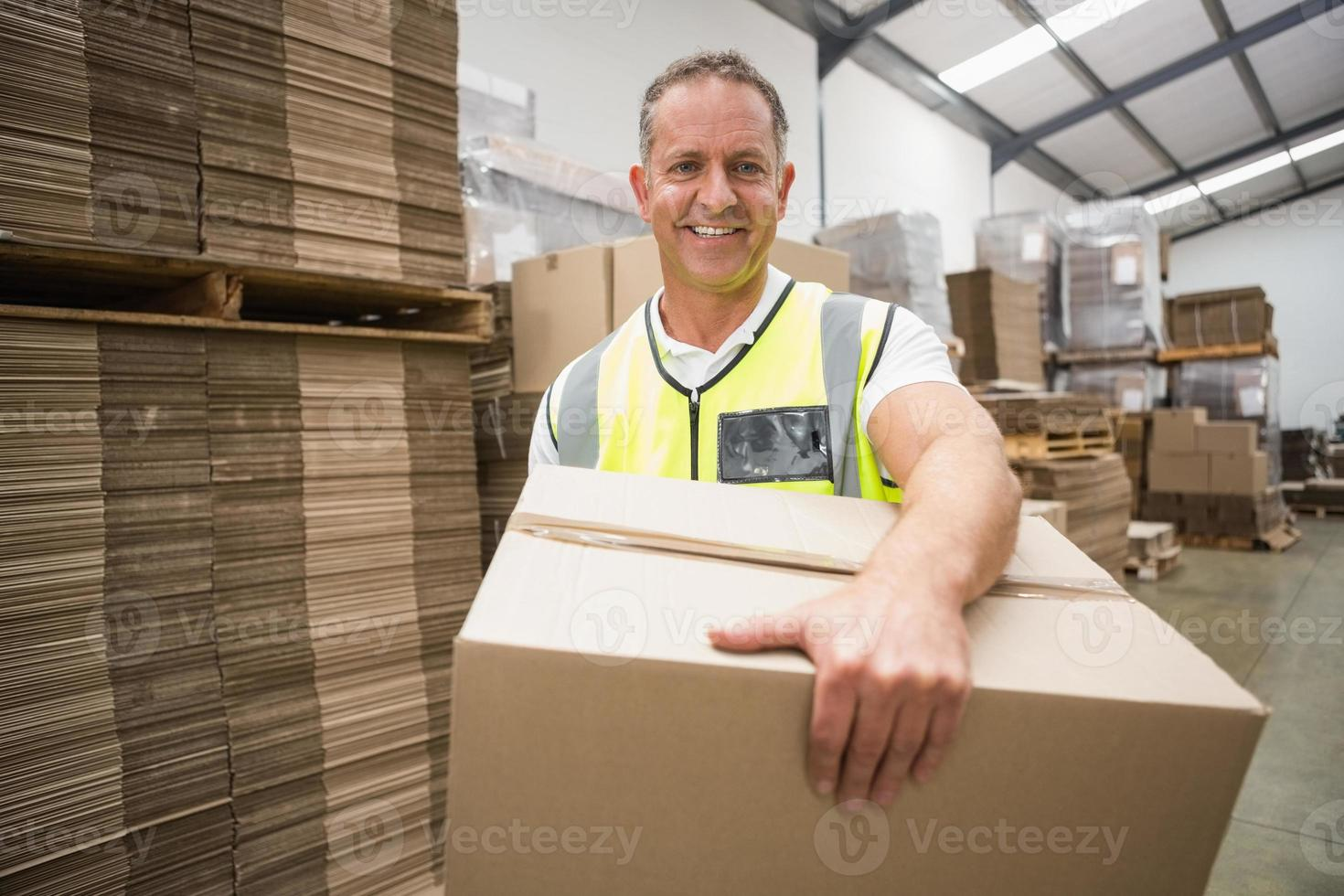 werknemer dragende doos in magazijn foto